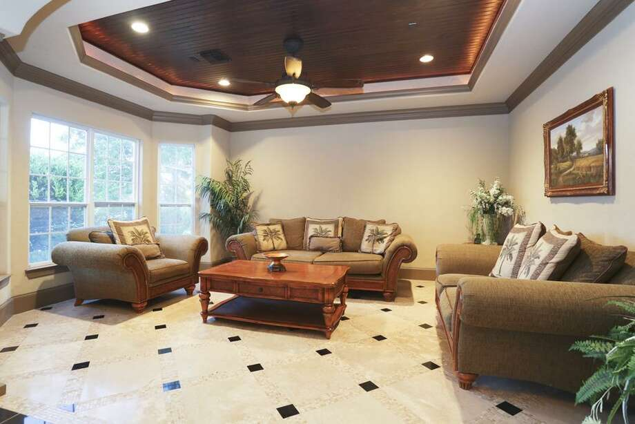 The formal living room shows the handcrafted wood ceiling and travertine, marble and stone flooring.