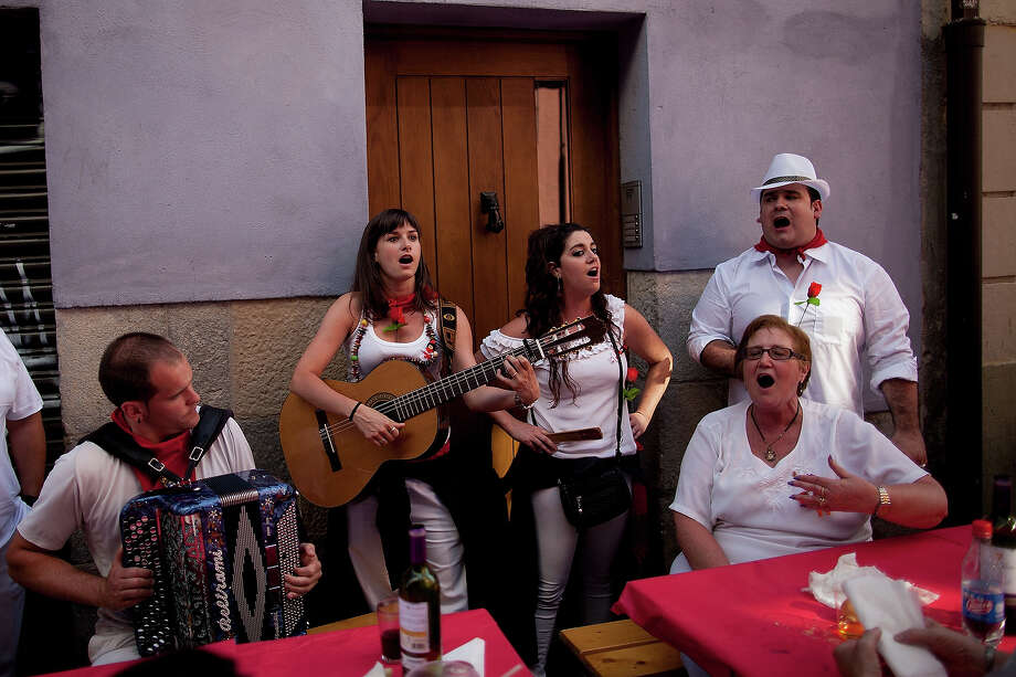 Revellers sing and play music at tables in the street after lunch during the third day of the San Fermin Running Of The Bulls festival, on July 8, 2013 in Pamplona, Spain. The annual Fiesta de San Fermin, made famous by the 1926 novel of US writer Ernest Hemmingway 'The Sun Also Rises', involves the running of the bulls through the historic heart of Pamplona, this year for nine days from July 6-14. Photo: Pablo Blazquez Dominguez, Getty Images / 2013 Getty Images