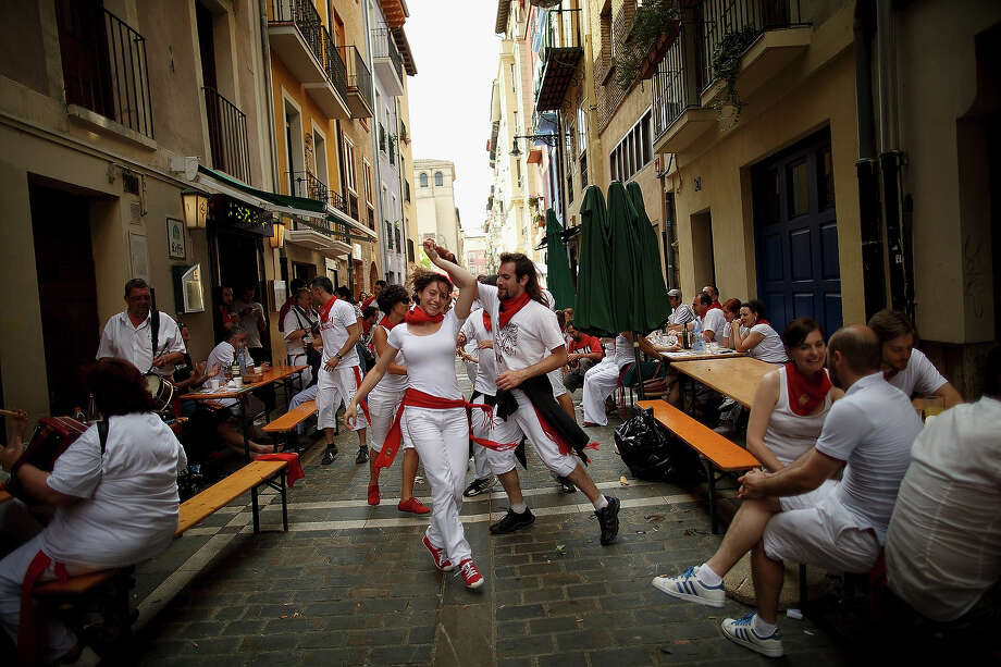 Revellers dance while musicians from Oberena play traditional Basque Country music in the street after having lunch on the fifth day of the San Fermin Running Of The Bulls festival on July 10, 2013 in Pamplona, Spain. The annual Fiesta de San Fermin, made famous by the 1926 novel of US writer Ernest Hemmingway 'The Sun Also Rises', involves the running of the bulls through the historic heart of Pamplona, this year for nine days from July 6-14. Photo: Pablo Blazquez Dominguez, Getty Images / 2013 Getty Images