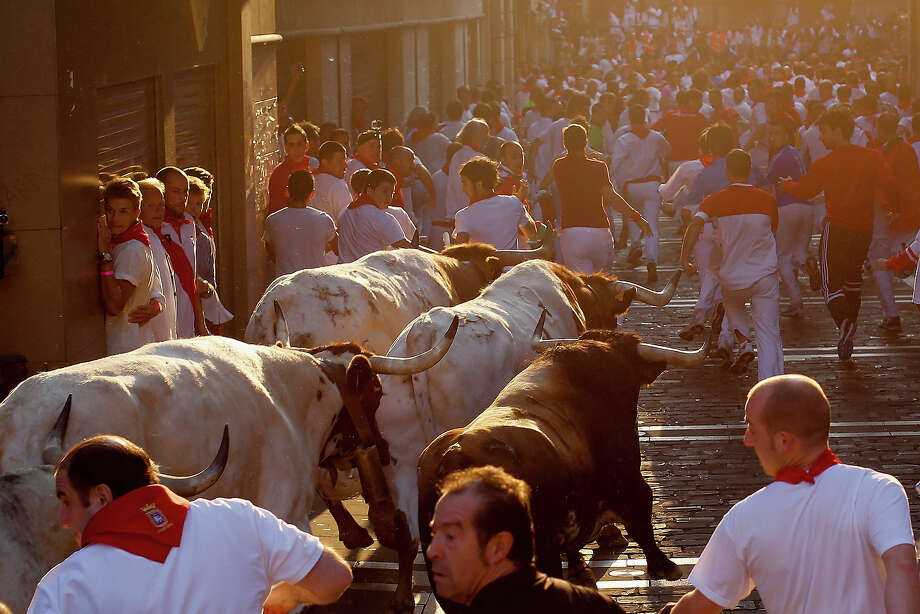Revellers run with Torrestrella's ranch fighting bulls at Calle Mercaderes during the sixth day of the San Fermin Running Of The Bulls festival on July 11, 2013 in Pamplona, Spain. The annual Fiesta de San Fermin, made famous by the 1926 novel of US writer Ernest Hemmingway 'The Sun Also Rises', involves the running of the bulls through the historic heart of Pamplona, this year for nine days from July 6-14. Photo: Pablo Blazquez Dominguez, Getty Images / 2013 Getty Images