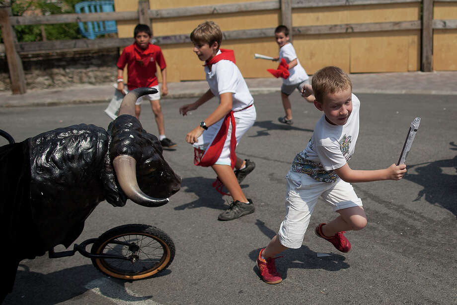 Children run in front of a toy bull during the Encierro Txiki (Little Bull Run) on the seventh day of the San Fermin Running Of The Bulls festival on July 12, 2013 in Pamplona, Spain. The annual Fiesta de San Fermin, made famous by the 1926 novel of US writer Ernest Hemmingway 'The Sun Also Rises', involves the running of the bulls through the historic heart of Pamplona, this year for nine days from July 6-14. Photo: Pablo Blazquez Dominguez, Getty Images / 2013 Getty Images