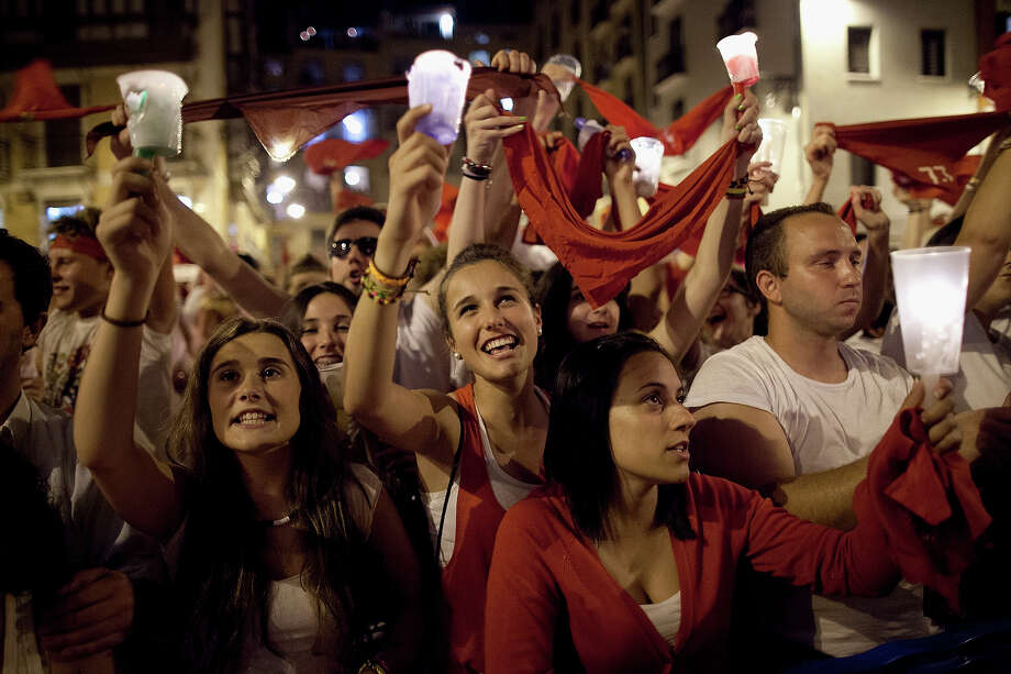 Revellers raise their scarves and candles as they sing the 'Pobre de Mi' song, marking the end of the San Fermin festival on July 15, 2013 in Pamplona, Spain. The annual Fiesta de San Fermin, made famous by the 1926 novel of US writer Ernest Hemmingway 'The Sun Also Rises', involves the running of the bulls through the historic heart of Pamplona, this year for nine days from July 6-14. Photo: Pablo Blazquez Dominguez, Getty Images / 2013 Getty Images
