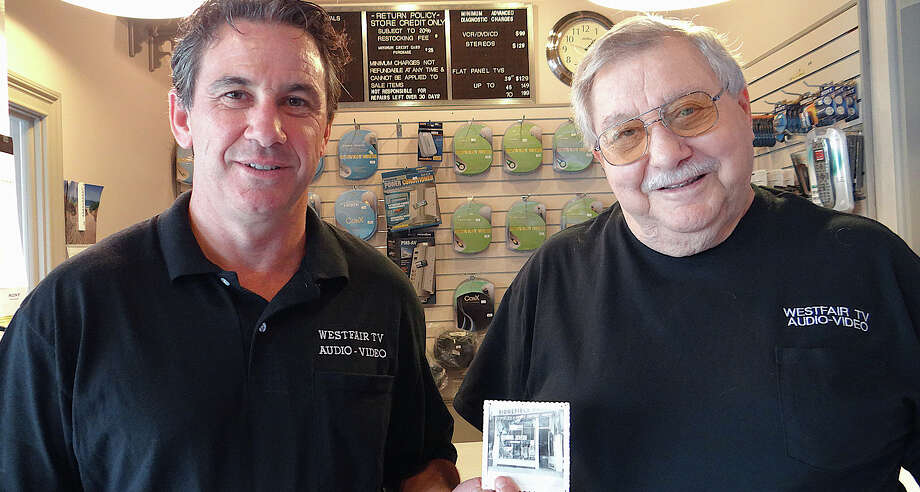 Glenn Levinson, left, owner of Westfair TV Audio, and his father, Mort, with a photo of Ridgefield Radio, which Mort started in 1958. The business became Westfair TV in 1963 when Mort moved his operation to the Westfair Shopping Center in 1963. Photo: Mike Lauterborn / Fairfield Citizen contributed