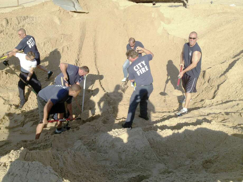 """Michigan City police and firefighters dig with shovels to rescue 6 year old Nathan Woessner, of Sterling, Ill., who was trapped for over three hours under about 11 feet of sand at Mount Baldy dune near Michigan City, Ind., on Friday July 12, 2013.  The boy, whose survival was described as a """"miracle"""" by a local coroner, remained in critical condition Saturday at Comer Children's Hospital in Chicago. Photo: Michigan City Fire Department Via The News Dispatch"""
