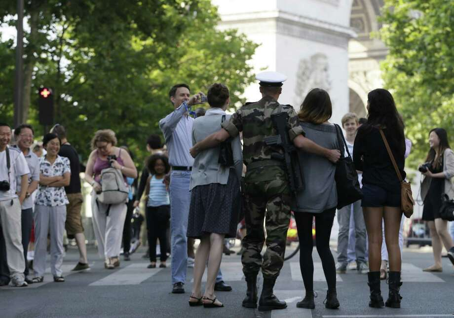 TOPSHOTS Women pose with a French soldier before the Bastille Day parade on the Champs Elysees avenue, on July 14, 2013 in Paris.    AFP PHOTO / KENZO TRIBOUILLARDKENZO TRIBOUILLARD/AFP/Getty Images Photo: KENZO TRIBOUILLARD, Getty / AFP