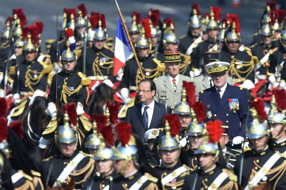TOPSHOTS French Army Chief of Staff Admiral Edouard Guillaud (R) and French President Francois Hollande review the troops with Mounted French Republican guards during the Bastille Day parade on the Champs Elysees, on July 14, 2013 in Paris.  AFP PHOTO / LIONEL BONAVENTURELIONEL BONAVENTURE/AFP/Getty Images ORG XMIT: - Photo: LIONEL BONAVENTURE, Getty / AFP