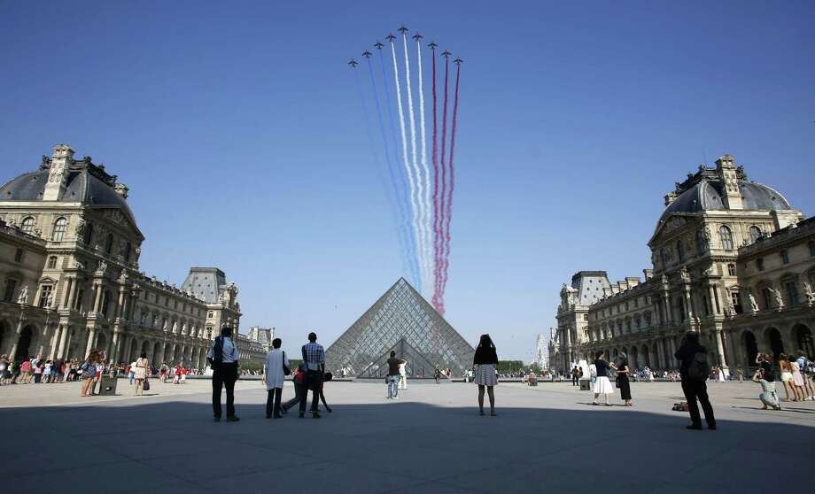 TOPSHOTS Nine alphajets from the French Air Force Patrouille de France releasing trails of red, white and blue smoke, colors of French national flag, fly over the Pyramid du Louvre during the Bastille Day parade, on July 14, 2013 in Paris.  AFP PHOTO / THOMAS COEXTHOMAS COEX/AFP/Getty Images ORG XMIT: 6 Photo: THOMAS COEX, Getty / AFP