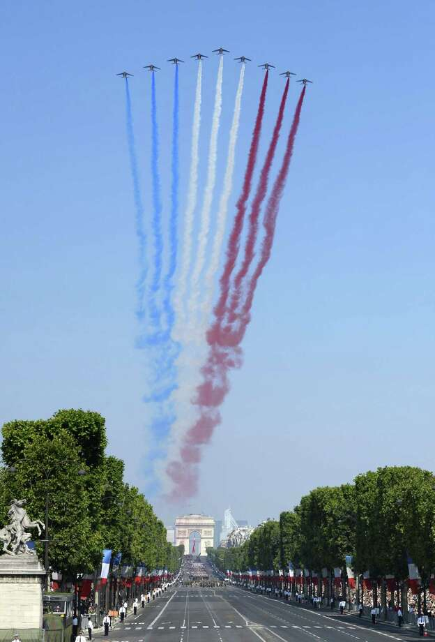 TOPSHOTS Nine alphajets from the French Air Force Patrouille de France release trails of red, white and blue smoke, the colors of French national flag, as they fly over the Place de la Concorde during the Bastille Day parade, on July 14, 2013 in Paris.  AFP PHOTO / LIONEL BONAVENTURELIONEL BONAVENTURE/AFP/Getty Images ORG XMIT: 77 Photo: LIONEL BONAVENTURE, Getty / AFP