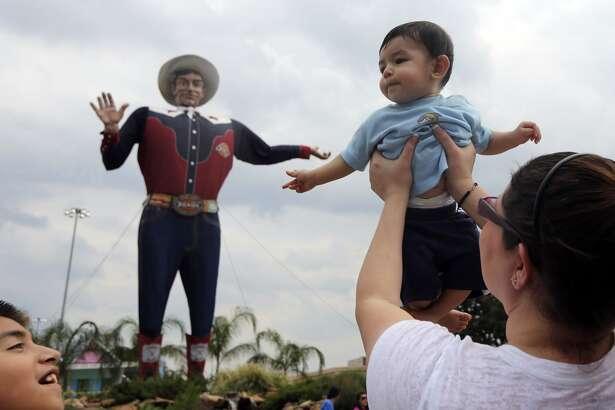 Six-month-old Baron Rodriguez, of Crandall, Texas, is held up by his mother Natasha Rodriguez for a photo with Big Tex as his brother Anthony Rodriguez, 11, looks on during the State Fair of Texas, Friday, Sept. 28, 2012, in Dallas. According to Natasha Rodriguez, she has held up each of her three children for a photo with Big Tex when they were infants. (AP Photo/LM Otero)