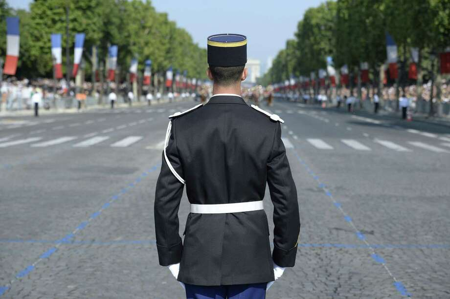 A member of the Gendarmerie watches the Bastille Day parade on the Champs-Elysees avenue, on July 14, 2013 in Paris.  AFP PHOTO / LIONEL BONAVENTURELIONEL BONAVENTURE/AFP/Getty Images ORG XMIT: 99 Photo: LIONEL BONAVENTURE, Getty / AFP
