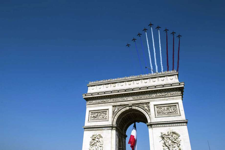French elite flying team Patrouille de France jets fly over the Arch of Triumph on the Place de l'Etoile on July 14, 2013 during the Bastille Day, the French National Day, parade in Paris.    AFP PHOTO / POOL / ETIENNE LAURENTETIENNE LAURENT/AFP/Getty Images Photo: ETIENNE LAURENT, Getty / AFP