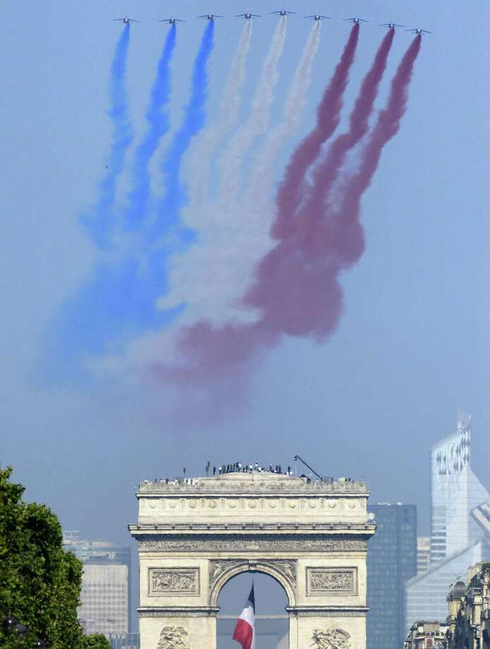 Nine alphajets from the French Air Force Patrouille de France releasing trails of red, white and blue smoke, colors of French national flag, fly over the Arc de Triomphe during the Bastille Day parade on the Champs Elysees avenue, on July 14, 2013 in Paris.  AFP PHOTO / LIONEL BONAVENTURELIONEL BONAVENTURE/AFP/Getty Images ORG XMIT: 7 Photo: LIONEL BONAVENTURE, Getty / Lionel Bonaventure