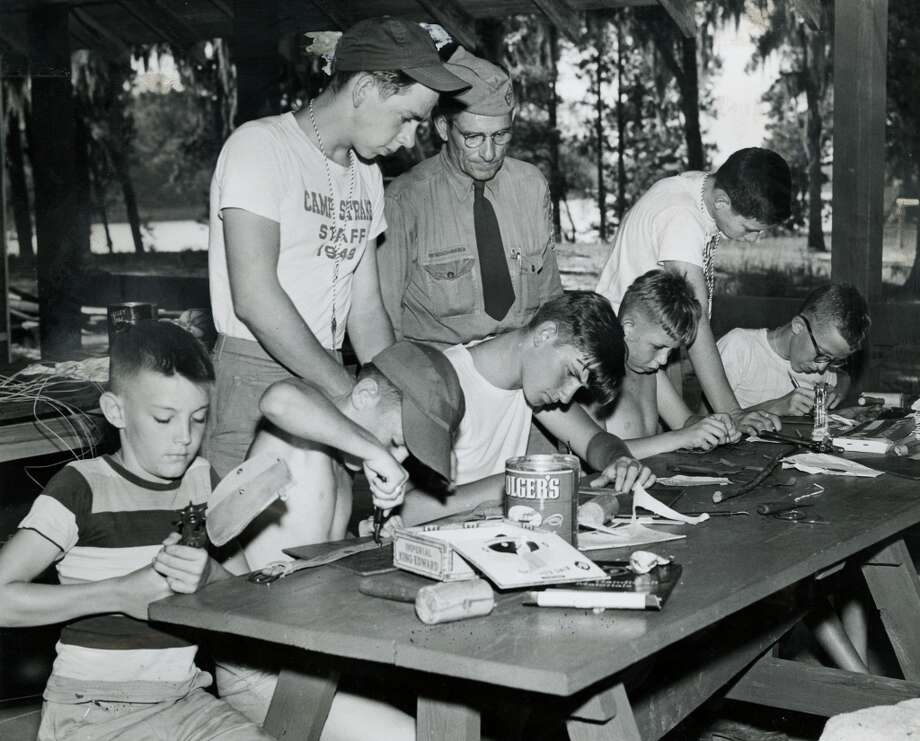 Teaching the scouts to make belts, lanyards and other leather crafts are (left to right, standing) counselor Bud Huffstutler; Scoutmaster Roy H. Smith; and counselor JImmy Strawn in June 1950. Photo: Gunnar Liljequist Jr., Houston Chronicle