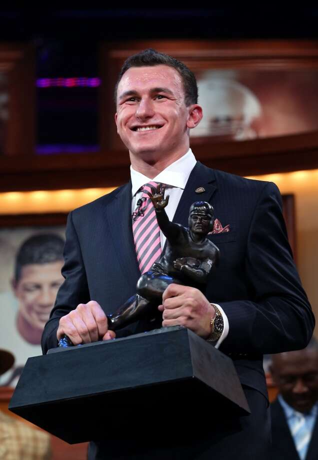 Texas A&M quarterback Johnny Manziel poses with the Heisman Trophy. Photo: Kelly Kline, Getty Images