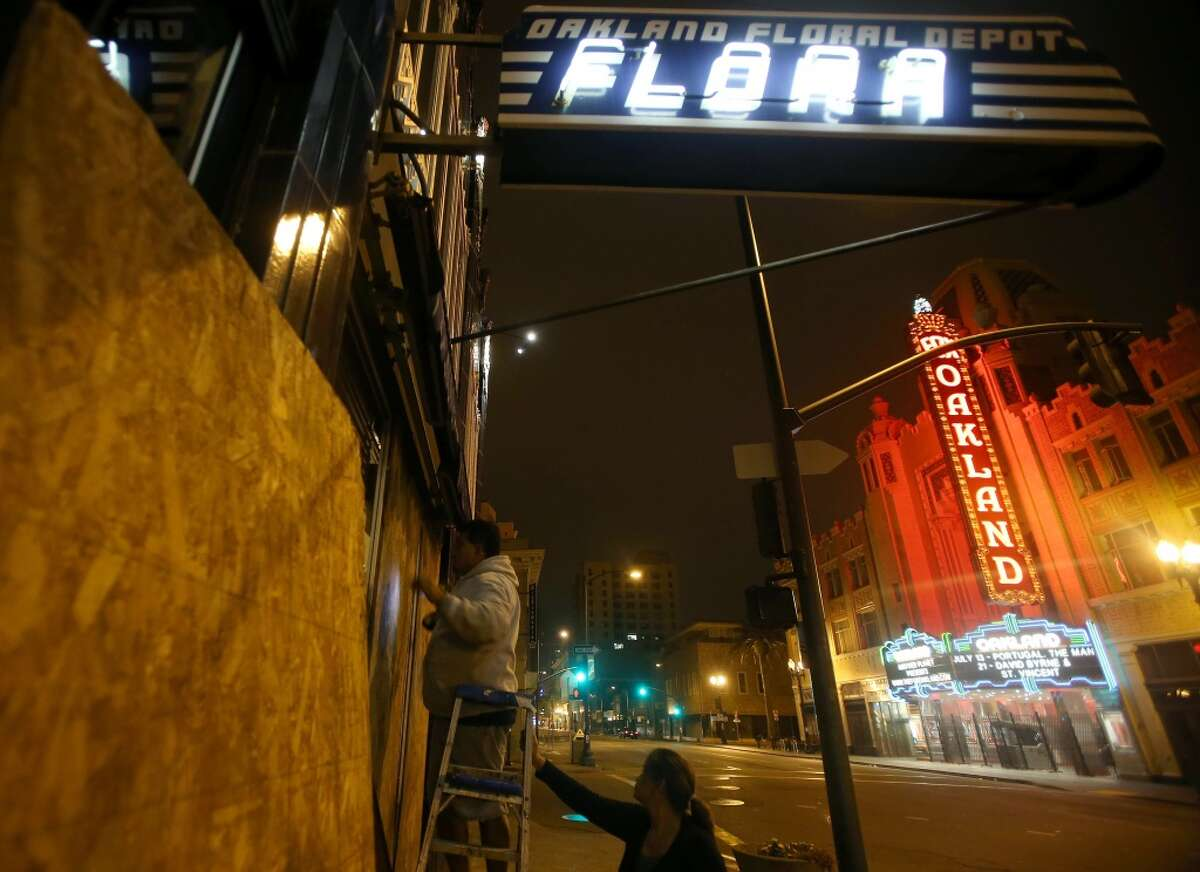 Workers board up windows at Flora restaurant in downtown Oakland.