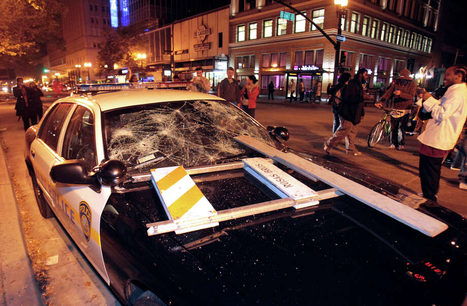 A BART police vehicle is vandalized during a protest after George Zimmerman was found not guilty in the 2012 shooting death of teenager Trayvon Martin, early Sunday, July 14, 2013, in Oakland, Calif. Protesters angered by the acquittal Zimmerman held largely peaceful demonstrations in three California cities, but broke windows and started small street fires Oakland, police said. (AP Photo/Bay Area News Group, Anda Chu) ORG XMIT: CAOAK109 Photo: Anda Chu, AP / The Tribune
