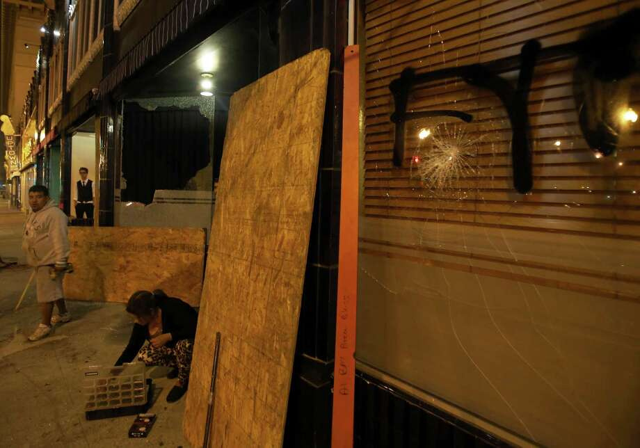 Workers board up windows at Flora restaurant in downtown Oakland, Calif., early Sunday, July 14, 2013, following protests after George Zimmerman was found not guilty in the 2012 shooting death of teenager Trayvon Martin. Protesters angered by the acquittal Zimmerman held largely peaceful demonstrations in three California cities, but broke windows and started small street fires Oakland, police said. (AP Photo/Bay Area News Group, Jane Tyska) ORG XMIT: CAOAK108 Photo: Jane Tyska, AP / The Tribune