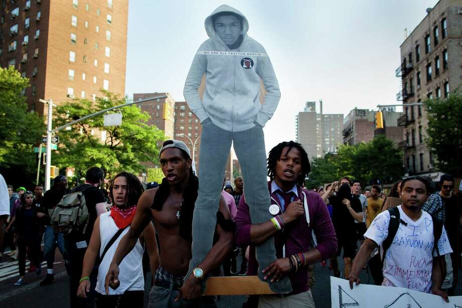 Demonstrators march through the Lower East Side neighborhood of Manhattan in New York, Sunday, July 14, 2013, holding a cut-out of Trayvon Martin during a protest against the acquittal of neighborhood watch member George Zimmerman in the killing of the 17-year-old in Florida. Demonstrators upset with the verdict protested mostly peacefully in Florida, Milwaukee, Washington, Atlanta and other cities overnight and into the early morning. (AP Photo/John Minchillo) ORG XMIT: NYJM113 Photo: John Minchillo, AP / FR170537 AP