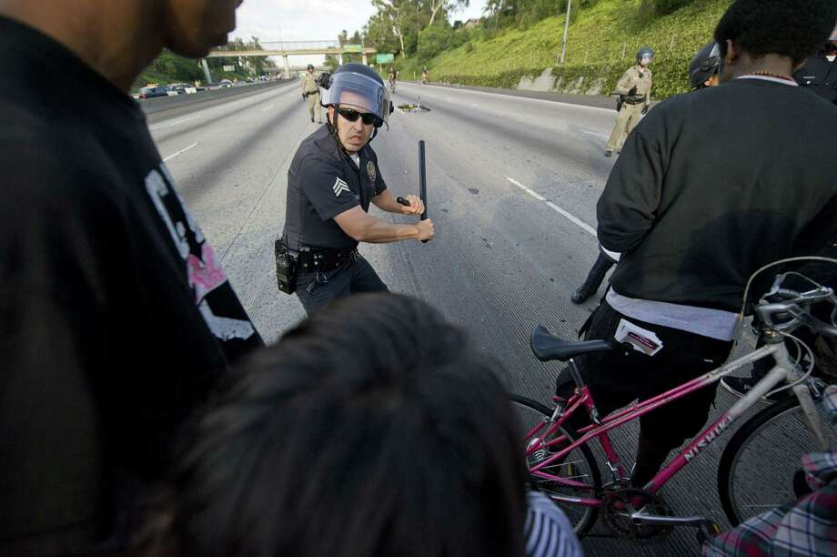 TOPSHOTS A police officer takes a defensive stance as he and colleagues hold a line stopping protestors from advancing on the 10 Freeway after demonstrators angry at the acquittal of George Zimmerman in the death of black teen Trayvon Martin walk onto the 10 Freeway stopping highway traffic, in Los Angeles, California July 14, 2013. A jury in Sanford, Florida late Saturday found Zimmerman, a volunteer neighborhood watchman, not guilty of shooting dead Martin, a 17 year-old unarmed teen on the night of February 26, 2012.  AFP PHOTO / ROBYN BECKROBYN BECK/AFP/Getty Images ORG XMIT: US-CRIME- Photo: ROBYN BECK, Getty / AFP
