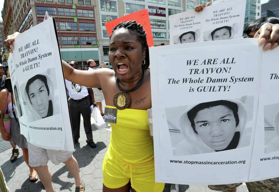 A woman holds signs during a demonstration in New York on July 14, 2013. Protests were held one day after a US jury found George Zimmerman not guilty of murdering unarmed black teen Trayvon Martin on February 26, 2012, in a racially charged trial that transfixed the country. The trial aroused strong passions among those who believed that Zimmerman -- a volunteer neighborhood watchman whose father is white and whose mother is Peruvian -- racially profiled and stalked Martin, and those convinced he acted in self-defense.     TOPSHOTS/AFP PHOTO/Stan HONDASTAN HONDA/AFP/Getty Images ORG XMIT: 173735708 Photo: STAN HONDA, Getty / AFP