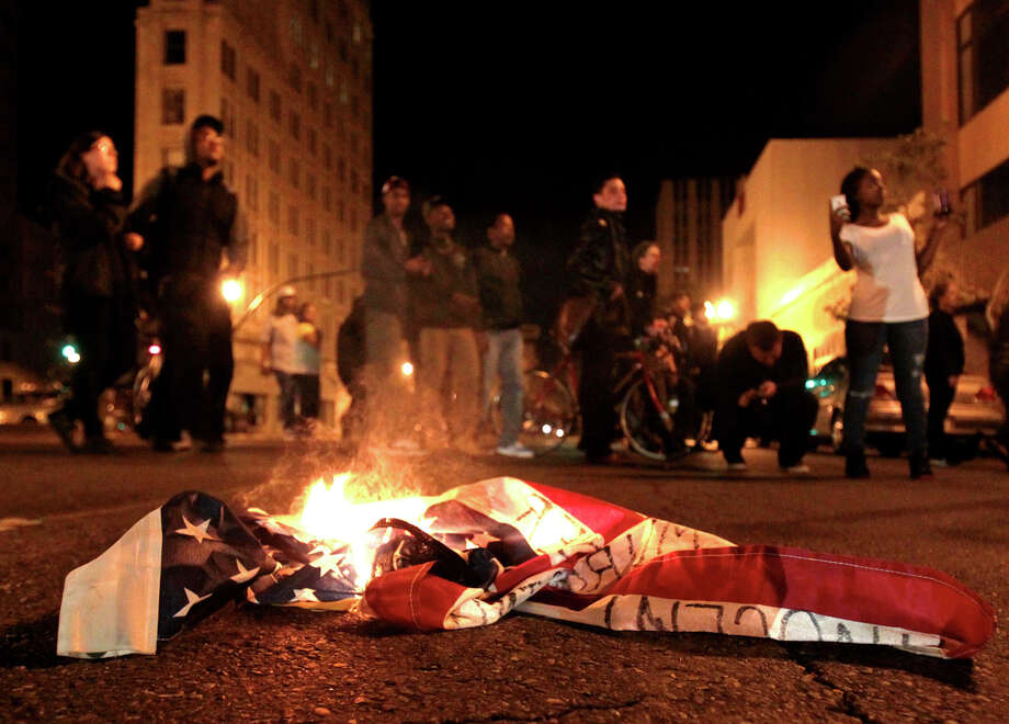 A flag burns during a protest after George Zimmerman was found not guilty in the 2012 shooting death of teenager Trayvon Martin, early Sunday, July 14, 2013, in Oakland, Calif. Protesters angered by the acquittal Zimmerman held largely peaceful demonstrations in three California cities, but broke windows and started small street fires Oakland, police said. (AP Photo/Bay Area News Group, Anda Chu) ORG XMIT: CAOAK103 Photo: Anda Chu, AP / The Tribune
