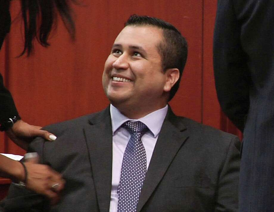 In this image from video, George Zimmerman smiles after a not guilty verdict was handed down in his trial at the Seminole County Courthouse, Sunday, July 14, 2013, in Sanford, Fla. Neighborhood watch captain George Zimmerman was cleared of all charges Saturday in the shooting of Trayvon Martin, the unarmed black teenager whose killing unleashed furious debate across the U.S. over racial profiling, self-defense and equal justice.  (AP Photo/TV Pool) ORG XMIT: FLJR221 Photo: Uncredited, AP / TV Pool