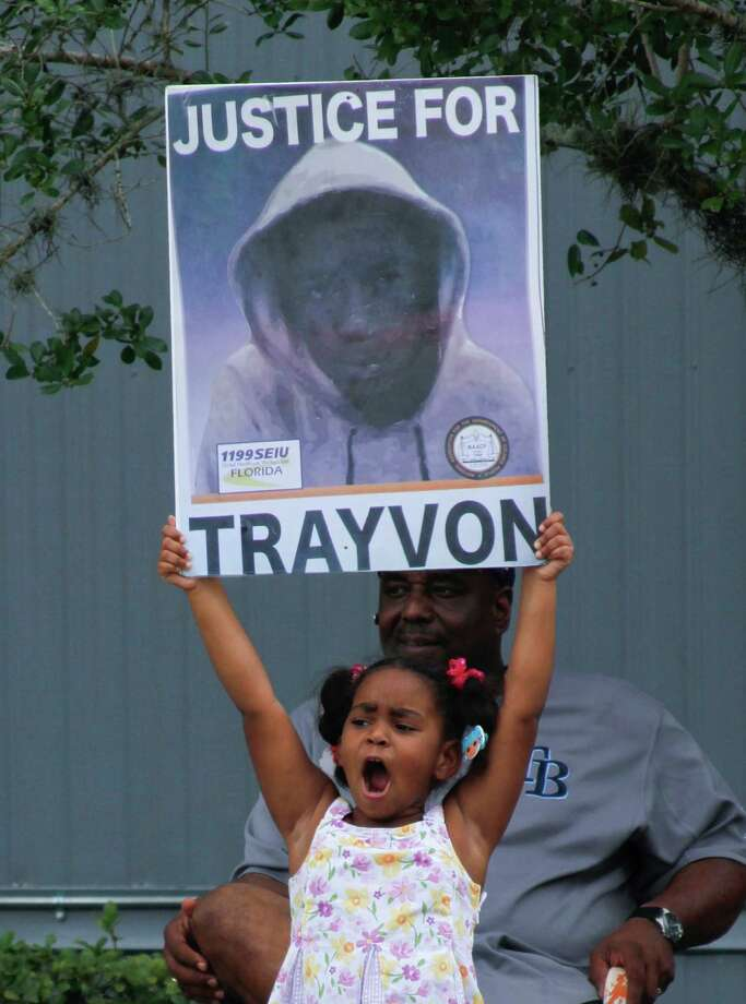 Hanna Brianna, 5, holds a sign in front of her home in the Goldsboro Historical neighborhood, Saturday, July 13, 2013, in Sanford, Fla. while residents wait for word on the verdict in the George Zimmerman trial. Zimmerman is charged with the 2012 shooting death of Trayvon Martin. (AP Photo/Mike Brown) ORG XMIT: FLJR108 Photo: Mike Brown, AP / FR170587 AP