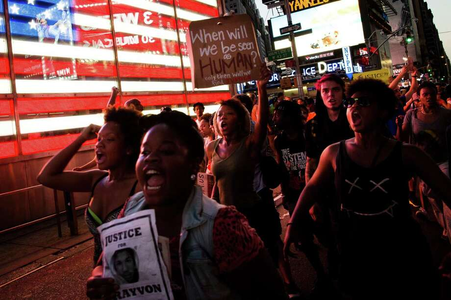 Demonstrators enter Times Square, Sunday, July 14, 2013, in New York, during a march against the acquittal of neighborhood watch member George Zimmerman in the killing of 17-year-old Trayvon Martin in Florida. Demonstrators upset with the verdict protested mostly peacefully in Florida, Milwaukee, Washington, Atlanta and other cities overnight and into the early morning. (AP Photo/John Minchillo) ORG XMIT: NYJM124 Photo: John Minchillo, AP / FR170537 AP