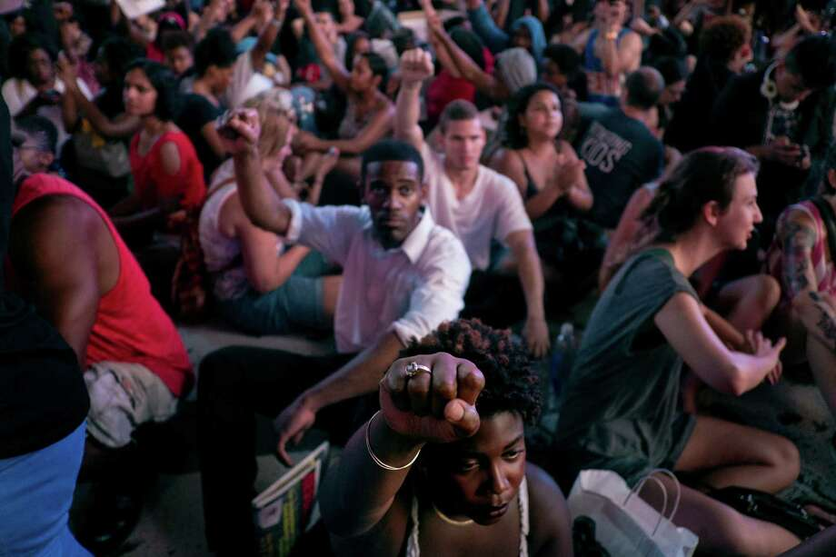 Marchers raise their fists as they sit down on Times Square, Sunday, July 14, 2013, in New York, for a protest against the acquittal of volunteer neighborhood watch member George Zimmerman in the 2012 killing of 17-year-old Trayvon Martin in Sanford, Fla. Demonstrators upset with the verdict protested mostly peacefully in Florida, Milwaukee, Washington, Atlanta and other cities overnight and into the early morning. (AP Photo/Craig Ruttle) ORG XMIT: NYCR107 Photo: Craig Ruttle, AP / FR61802 AP