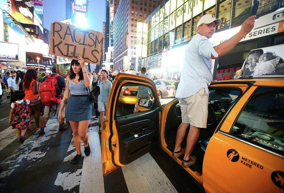 NEW YORK, NY - JULY 14:  A man stands on a taxicab blocked by protesters to take pictures as people rally in support of Trayvon Martin in Times Square while blocking traffic in Manhattan on July 14, 2013 in New York City. George Zimmerman was acquitted of all charges in the shooting death of Martin July 13 and many protesters questioned the verdict.  (Photo by Mario Tama/Getty Images) ORG XMIT: 173735708 Photo: Mario Tama, Getty / 2013 Getty Images
