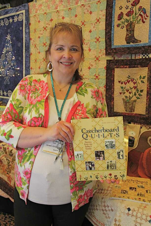 Rose Ann Cook, owner of Quilter's Emporium in Stafford, holds her quilt book she wrote, Czecherboard Quilts. Photo: Suzanne Rehak, For The Chronicle