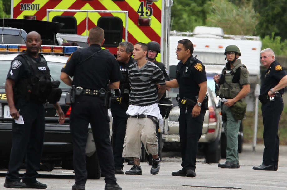 San Antonio police detain a suspect (center, wearing stripes) after a standoff took place Monday morning July 15, 2013 on the 7500 block of Barryhill. Police arrested a total of 10 people after a home invasion took place at a different residence on the 7300 block of Clear Water. Police said they will obtain a warrant to search the home on Barryhill. Photo: JOHN DAVENPORT, SAN ANTONIO EXPRESS-NEWS / ©San Antonio Express-News/Photo may be sold to the public