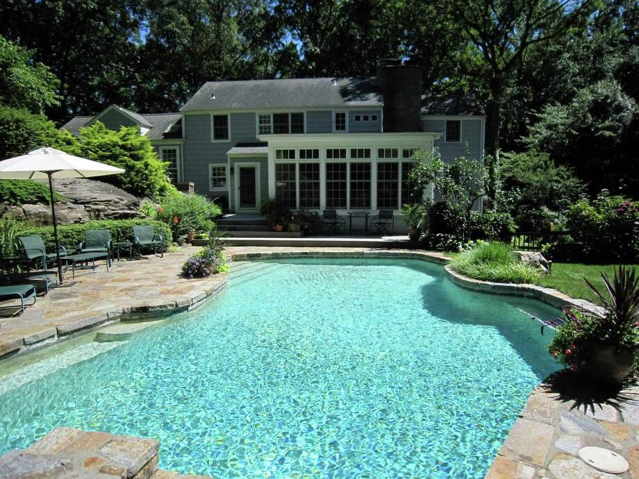 The 1940 Colonial at 22 Stony Brook Road in Darien, on the market for $2,195,000, has a backyard pool that is surrounded by exquisite landscaping and a stone patio that blends into a finely planted ledge that disappears into surrounding woods. Photo: Contributed