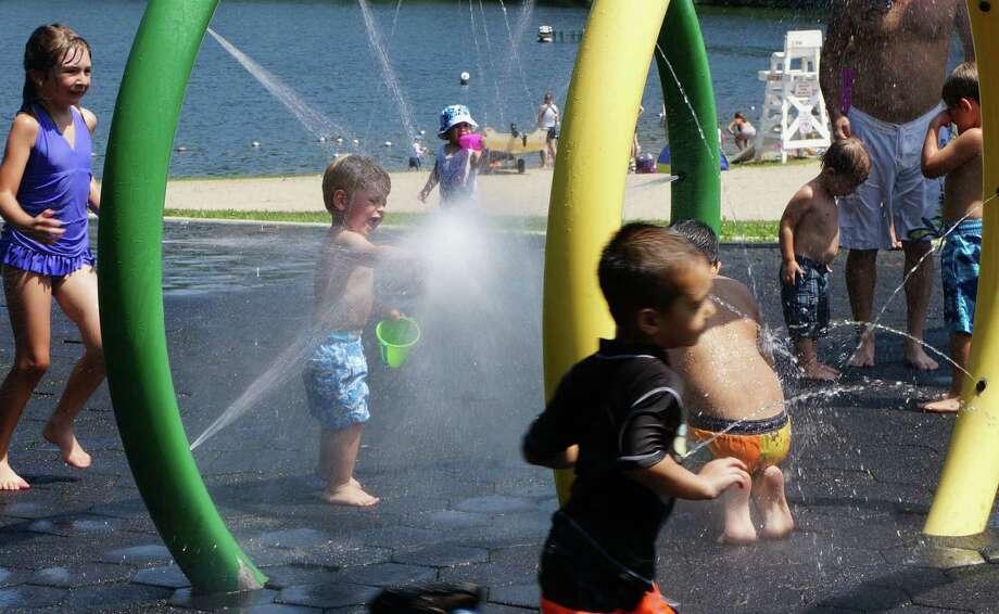One way to beat the heat Monday was a run through the sprinkler park at Lake Mohegan. Photo: Genevieve Reilly / Fairfield Citizen