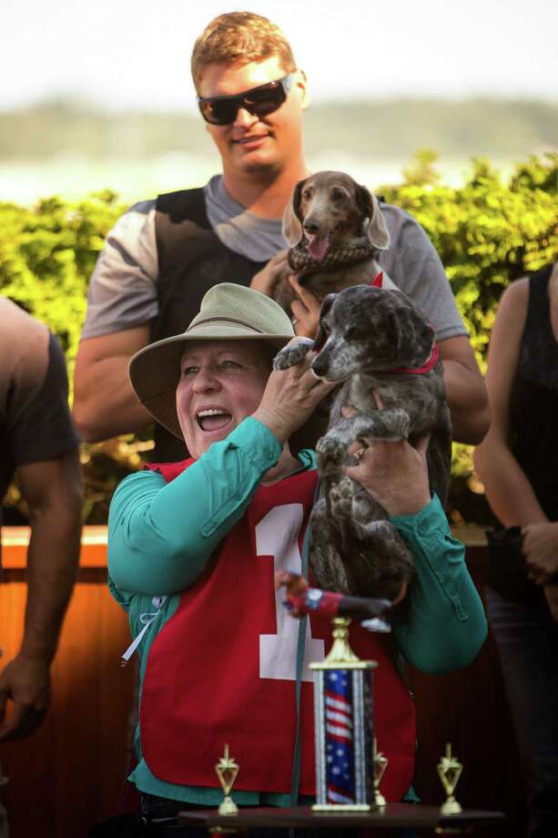 Owner Gretchen Howell, in red, holds her miniature dachshund, Ben Norman, the first place winner two years in a row, following the conclusion of the 17th Annual Kent & Alan Wiener Dog Races Sunday, July 14, 2013, at Emerald Downs in Auburn. Three heats of short-legged competition had crowds cheering and participating dog owners rooting for their own little canine athlete. Photo: JORDAN STEAD, SEATTLEPI.COM / SEATTLEPI.COM