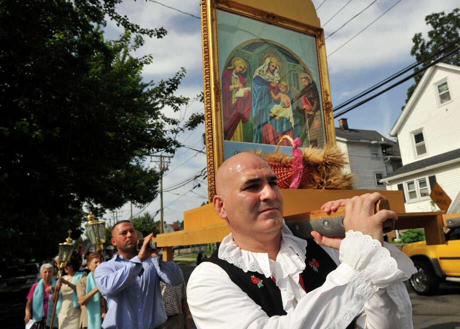 Marco Orsaia carries one corner of the Madonna della Grazie, the patron saint of Minturno, Italy, during the Minturnese community's tenth annual Sagra delle Regne, or harvest festival, procession in Stamford on Sunday, July 14, 2013. The Stamford festival is celebrated simultaneously with its sister city of Minturno, Italy, Photo: Jason Rearick / Stamford Advocate
