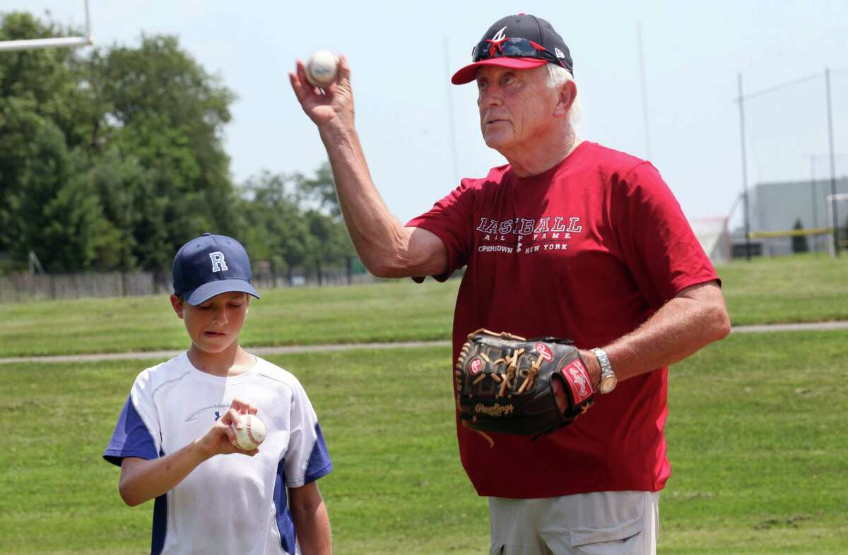 Major League Baseball Hall of Famer Phil Niekro helps Max Chermayoff, 12, of Rowayton, with his knuckleball at a Baseball World Training School in Westport, Conn. on Monday, July 15, 2013.