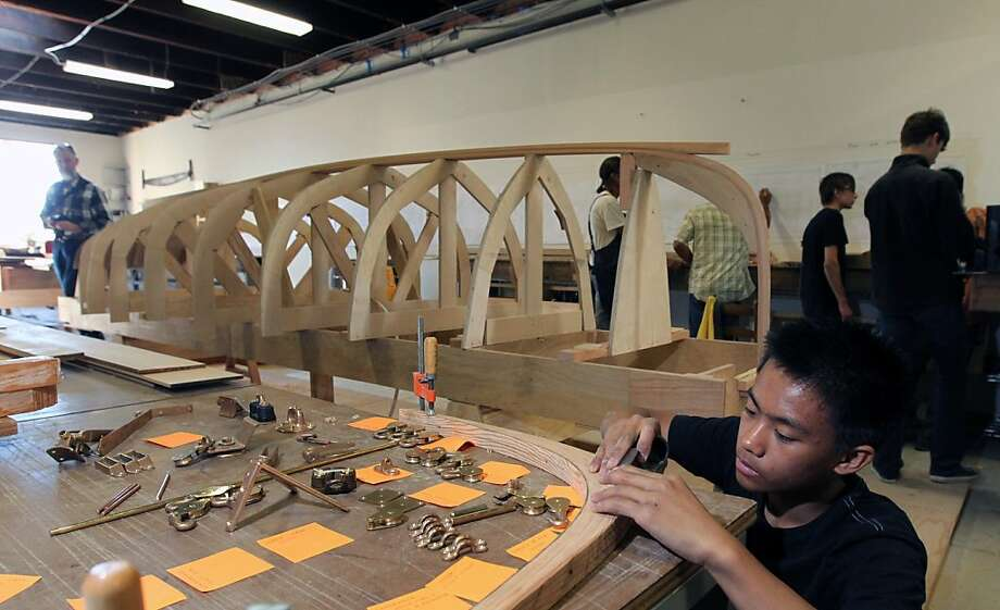 Nilo Batle, 14, planes down a stem, as the hull of a sailboat from a 19th century design takes shape in the rear. Photo: Lance Iversen, The Chronicle