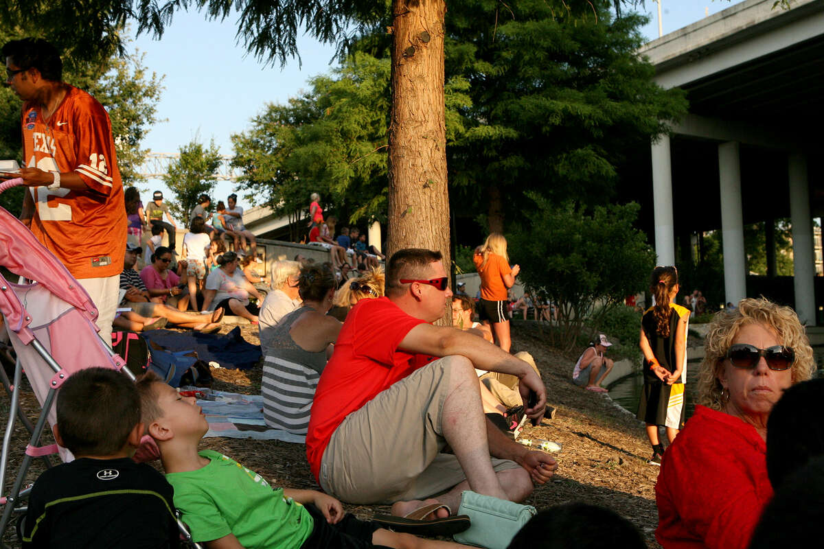 Families gather along the San Antonio River Walk July 9 to see bats emerge from under the Interstate 35 overpass during a Bat Loco event, where there are activities for children and an informative presentation on bats until the bats come out.