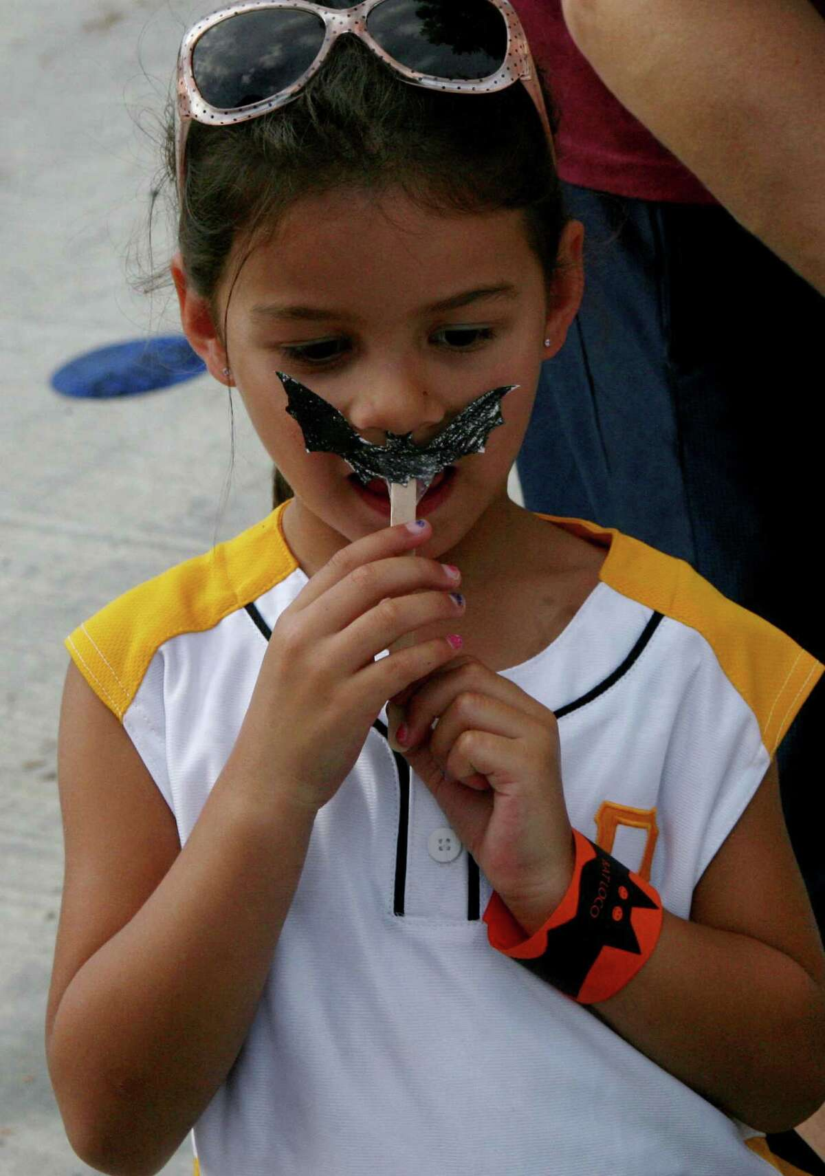 Alana Stanford uses a bat that she cut out as a mustache during a Bat Loco event.
