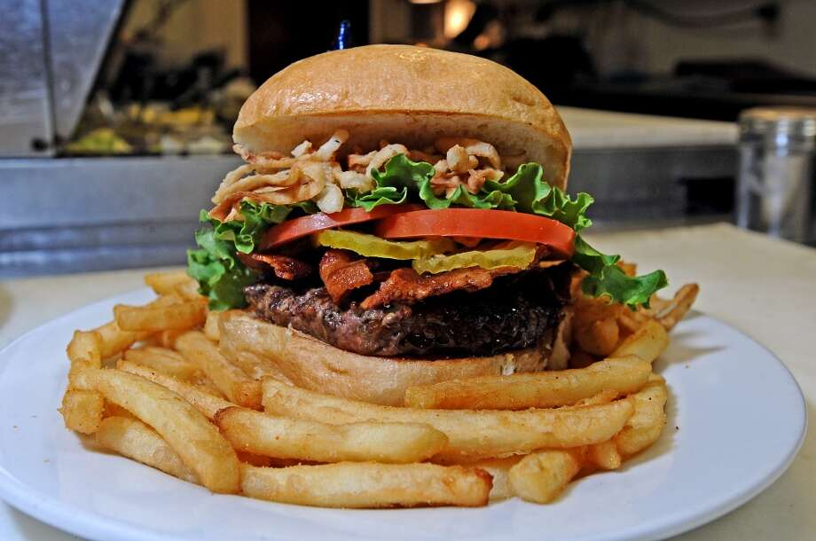 The Bourbon Bacon Burger at Madison's consist of a half pound bourbon glazed patty with applewood smoked bacon, onion straws, and pickles.   Photo taken: Randy Edwards/The Enterprise