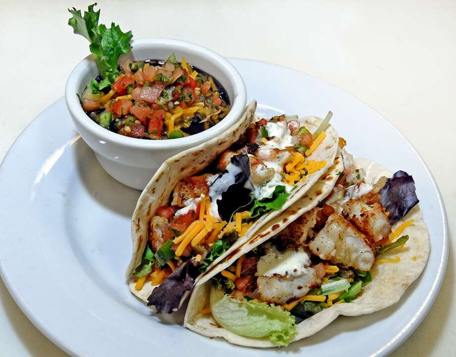 The Shrimp of Fish Tacos from Madison's consist of grilled shrimp or fish inside fresh flour tortillas, mixed greens, pico de gallo and spicy jalapeno ranch with black beans and rice.  Photo taken: Randy Edwards/The Enterprise