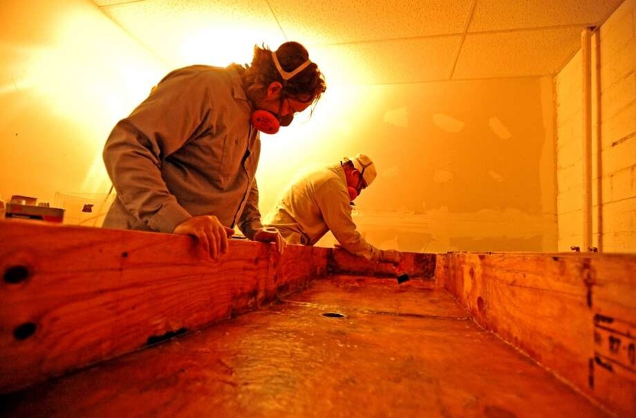 Joe Winston, left, and Beau Dumesnil, right, work on fiber-glassing the existing sink for the Art Studio Darkroom Friends who are dedicated to the reconstruction of the Black and White photography lab at the Art Studio Inc. Photo taken: Randy Edwards/The Enterprise