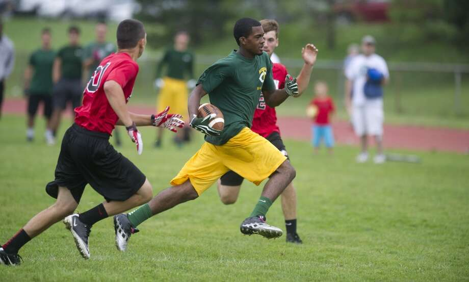"""Trinity Catholic's Neno Merritt carries the ball during Saturday's """"Grip It and Rip It"""" high school football passing camp and competition at New Canaan High School on July 13, 2013."""