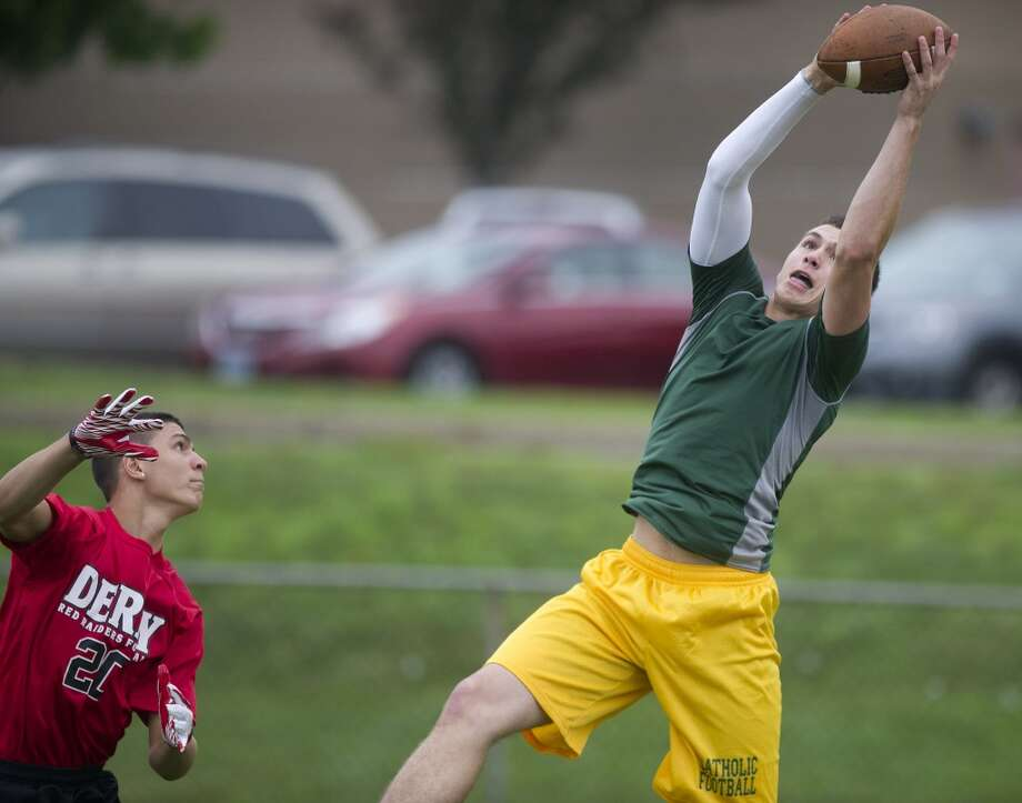"Trinity Catholic's Connor Amann makes a catch during Saturday's ""Grip It and Rip It"" high school football passing camp and competition at New Canaan High School on July 13, 2013."