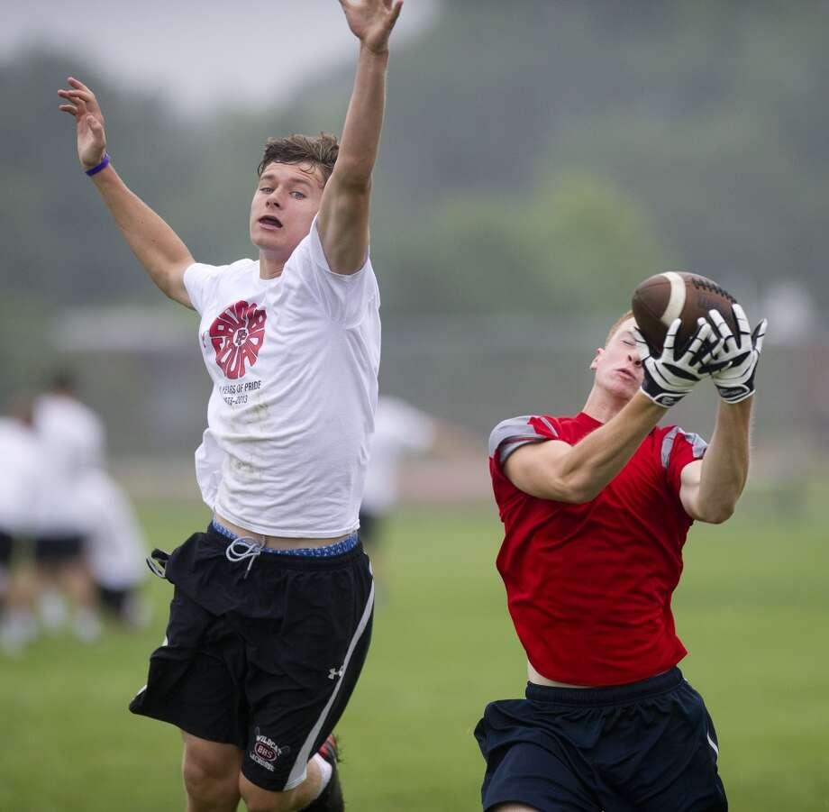 "Fairfield Prep's Jake Buckley, left, and Greenwich's Devin McGrath, right, play in Saturday's ""Grip It and Rip It"" high school football passing camp and competition at New Canaan High School on July 13, 2013."