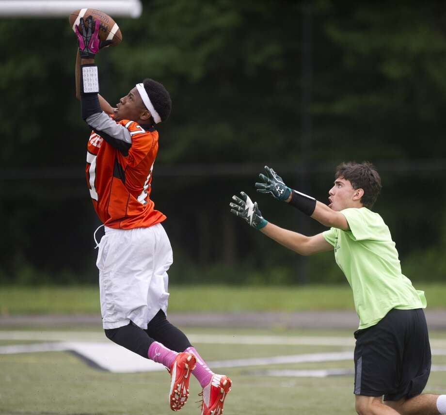 "Patrick Dircile of Stamford jumps to make a catch as New Milford's Grant Murphy looks on during Saturday's ""Grip It and Rip It"" high school football passing camp and competition at New Canaan High School on July 13, 2013."