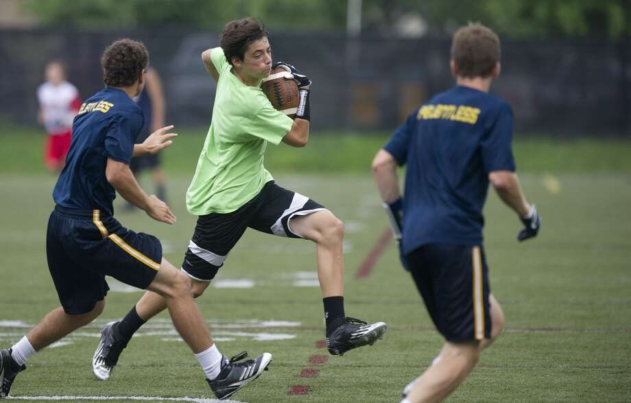 "New Milford's Trevor Hallas carries the ball during Saturday's ""Grip It and Rip It"" high school football passing camp and competition at New Canaan High School on July 13, 2013."