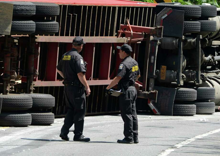 A tractor trailer lies on is its side after rolling over in an accident that involved the truck and two cars Monday mroning, July 15, 2013, in Hoosick N.Y.  One person was transported to Albany Medical Center by helicopter and two were taken to local hospitals by ambulance.   ( Skip Dickstein/Times Union ) Photo: Skip Dickstein / 00023169A