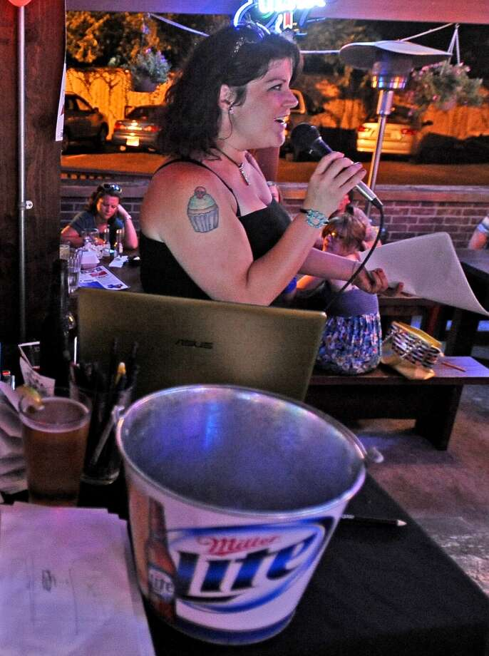 Robbi Murphy announces for the Geeks Who Drink trivia game on Tuesday, July 2, 2013, at Luke's. Photo taken: Randy Edwards/The Enterprise